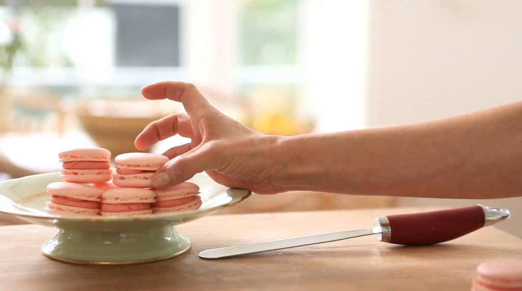 Hand taking a French macaron cookie from a green cake stand