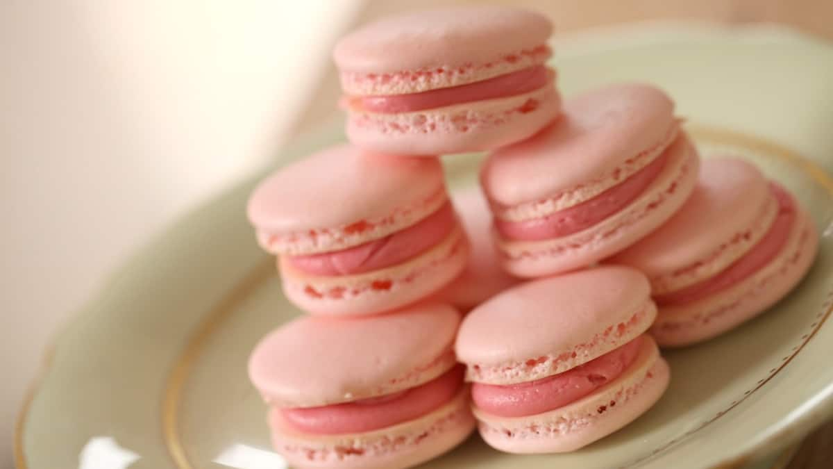 Pink French macarons filled with raspberry buttercream on a pale green cake stand