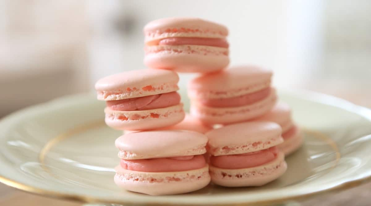 a plate of French Macarons filled with buttercream stacked on a cake stand