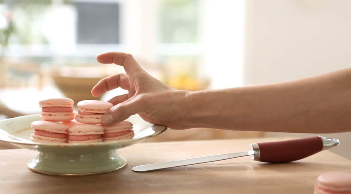 a person placing a finished French Macaron cookie on a cake stand