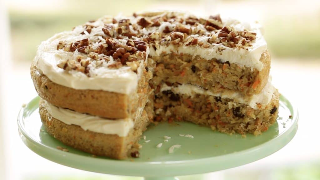 Carrot Cake Recipe cut open and served on a green cake plate