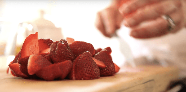 strawberries being cut for Coconut Ice Cream Baskets with Strawberry Sauce