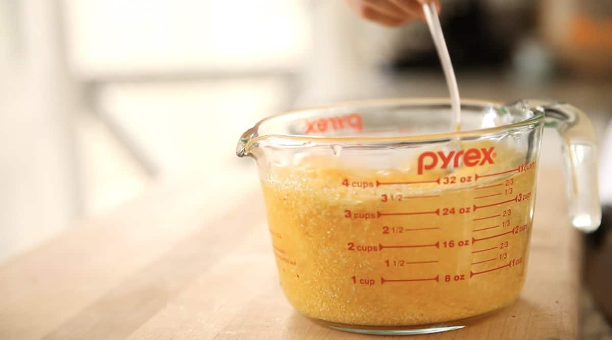 a person stirring water and polenta in a Pyrex pitcher