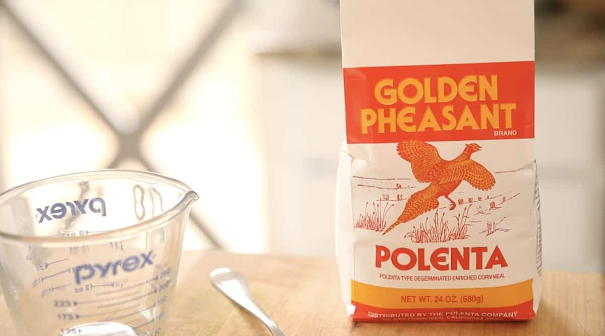 a bag of polenta on a cutting board with Pyrex Pitcher