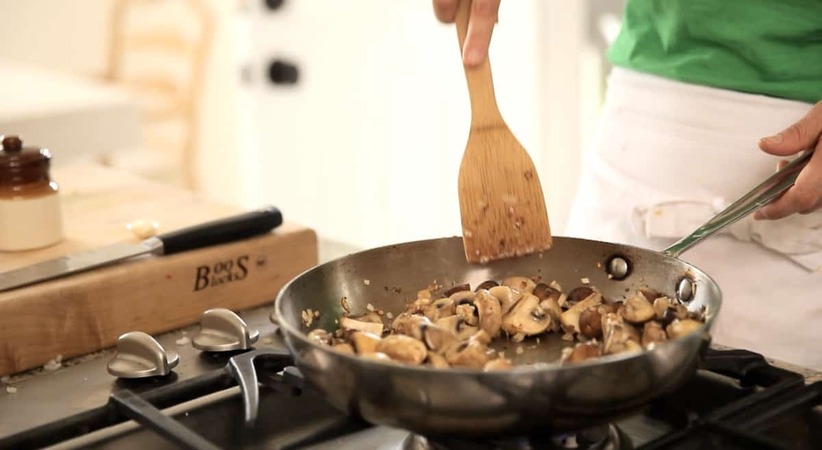 Cooking mushrooms in a pan with a wooden spoon