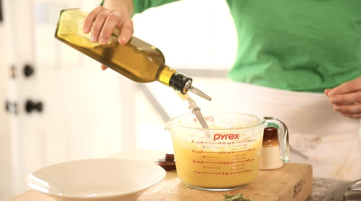 a person adding olive oil to cooked polenta in a Pyrex pitcher