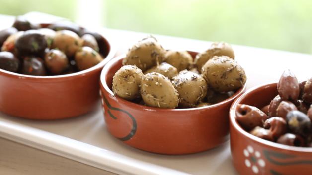 Olives in terra cotta dishes on a white rectangular platter