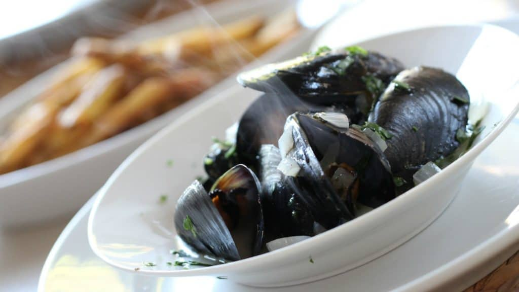 Easy Moules Frites served in a white bowl on a white plate