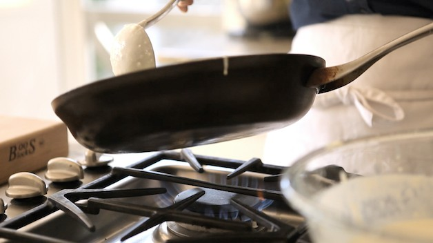 ladling out crepe batter into a non stick pan