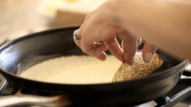 flipping crepe in a pan