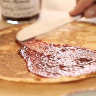 spreading raspberry jam on a crepe