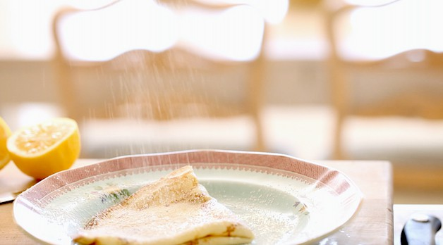 Dusting powdered sugar on a folded crepe on a plate