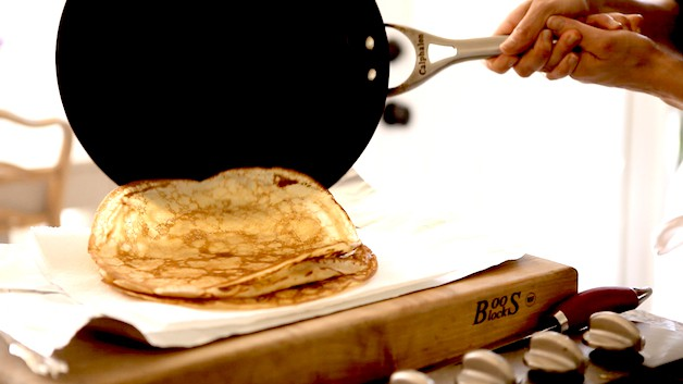 Sliding a crepe off a pan onto a cutting board