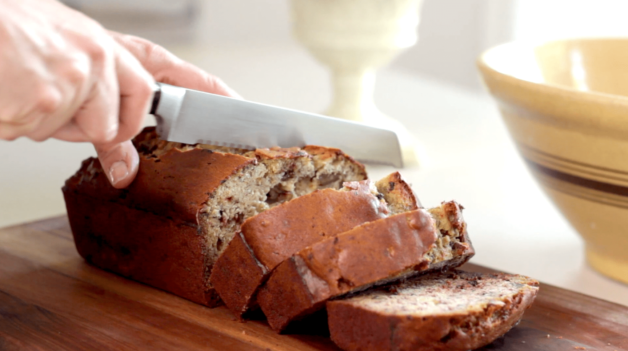 Ultimate Banana Bread Recipe being sliced on a cutting board
