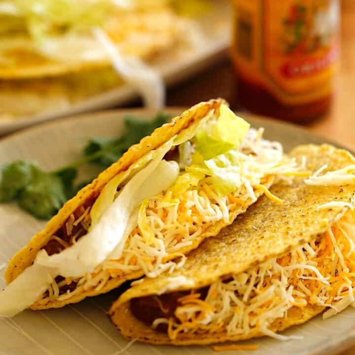 A plate of two crispy ground beef tacos on a plate topped with cheese and lettuce