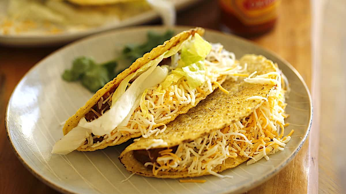 Crispy Tacos filled with ground beef, cheese and lettuce on a plate