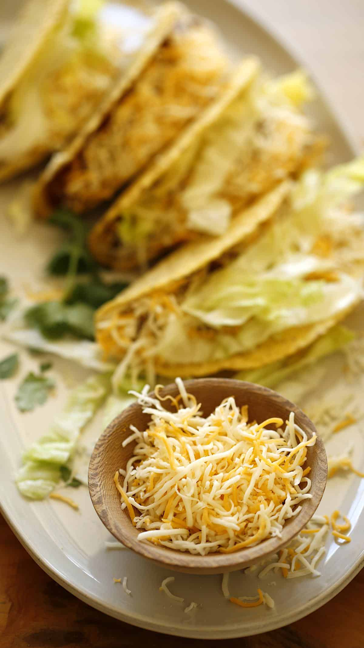 a platter of slow cooker tacos on a platter with a small bowl of shredded cheese
