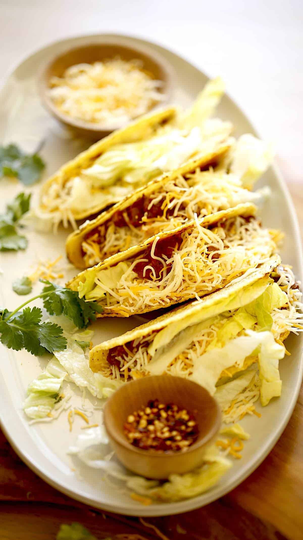 A platter of slow cooker beef tacos yopped with cheese and lettuce