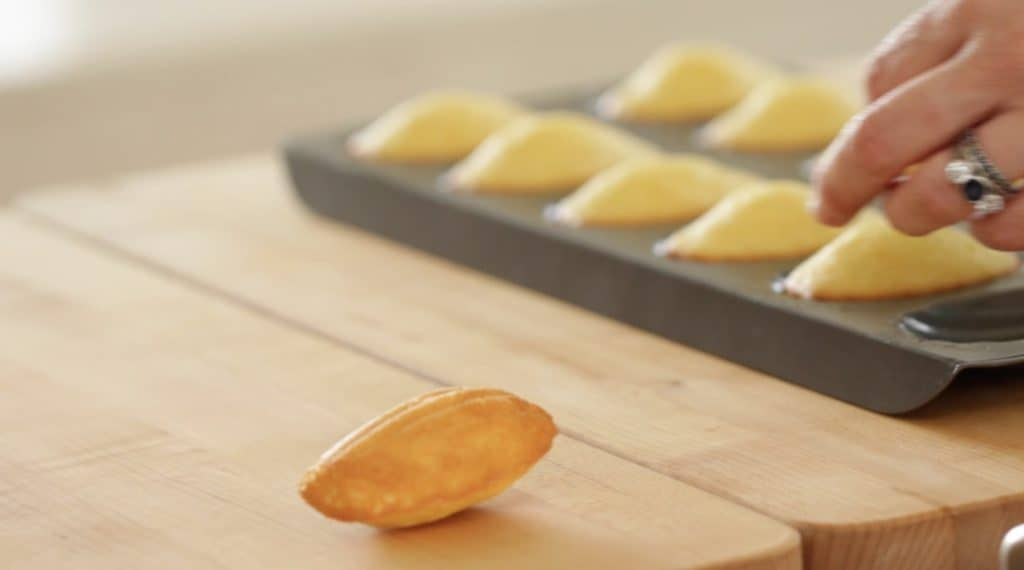 Madeleine cookie being removed from madeleine cookie pan from an Easy Madeleine Recipe