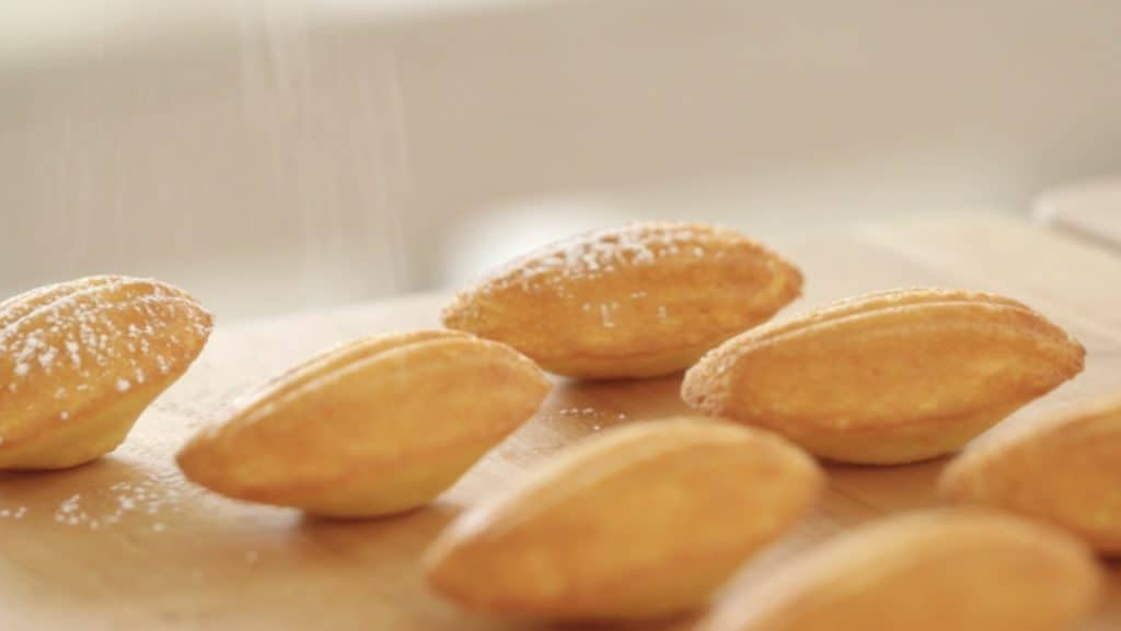 Easy Madeleine Recipe being dusted with powdered sugar