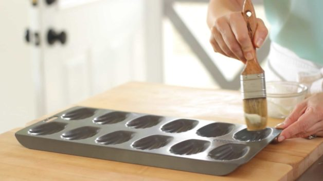 Madeleine cookie tin being brushed with non-stick baking spray and pastry brush for an Easy Madeleine Recipe