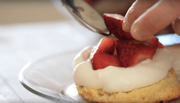 How to make a strawberry shortcake being assembled with a spoon and hand