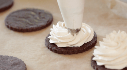 Detail shot of whipped cream filling being piped on a cookie from a pastry bag with star tip