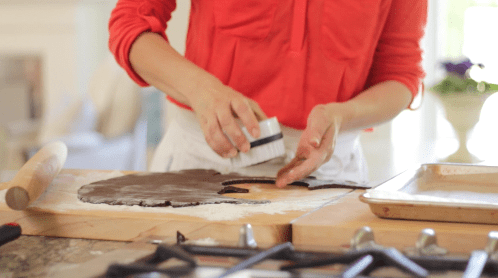Cutting chocolate cookie dough into circles with a scalloped cookie cutter