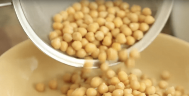 chickpeas being added to a bowl for an easy hummus recipe