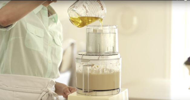 olive oil being added to an easy hummus recipe in a food processors
