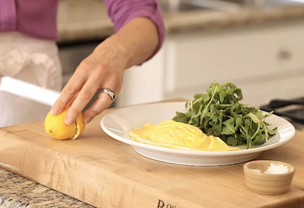 Omelette and salad on a plate with a side salad of aurugula, hand slices lemon