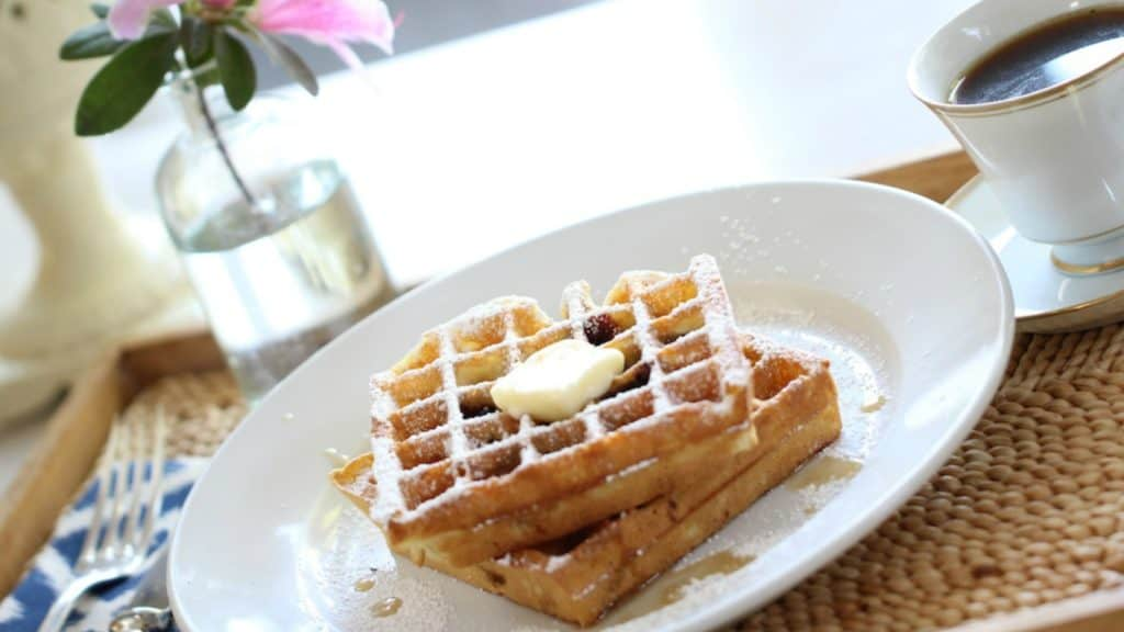 Blueberry Waffle Recipe served on a white plate with a pat of butter and syrup on the waffles