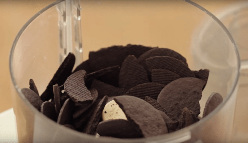 chocolate wafer cookies being crushed in a food processor for a how to make a chocolate mousse cake recipe