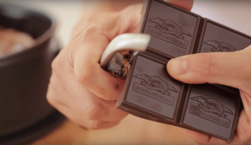 a vegetable peeler peeling a chocolate bar for a how to make a chocolate mousse cake recipe