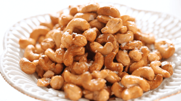 Honey Cashews in a white bowl topped with sea salt flakes