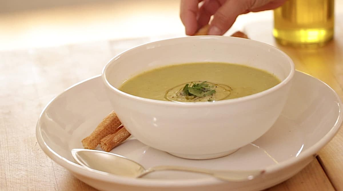 a person adding breadsticks to a Vegan cream of broccoli soup