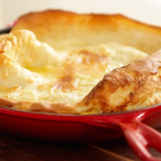 Dutch Baby Pancake Recipe in a red skillet served oven to table