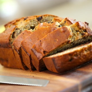 Banana Bread sliced on a cutting board with a knife