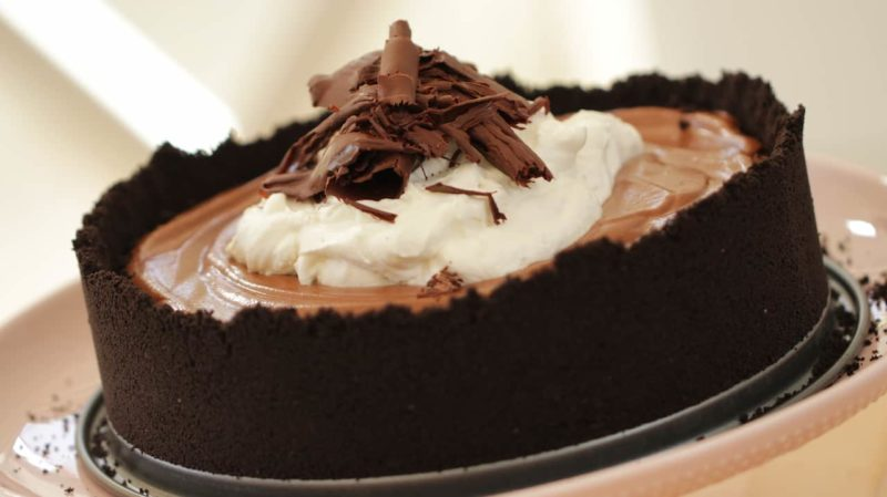up close of a How to Make a Chocolate Mousse Cake recipe served on a pink cake stand