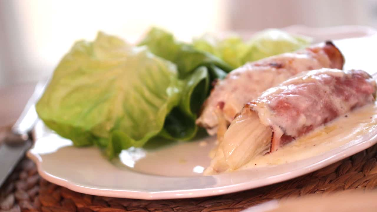 Endive Bechamel and tossed salad on a white plate