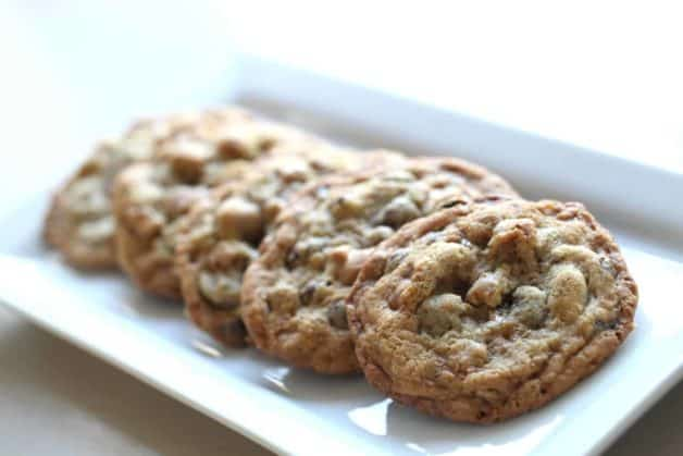 5 chocolate chip cookies piled on a rectangular white plate