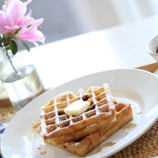 Blueberry Waffle Recipe served on a white plate on a tray with a cup of coffee and flowers in the background