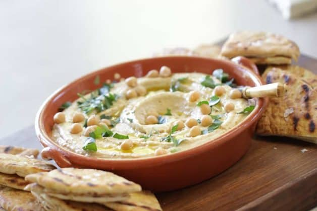 Hummus dip and grilled pita bread on board served with pita