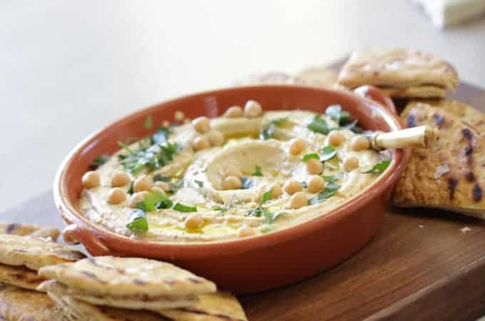 Authentic Hummus Recipe served in a bowl on a wood surface with grilled pita bread
