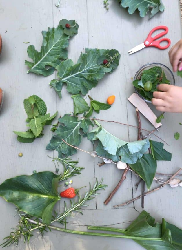 Leaves and natural materials on a table with scissors and child's hand