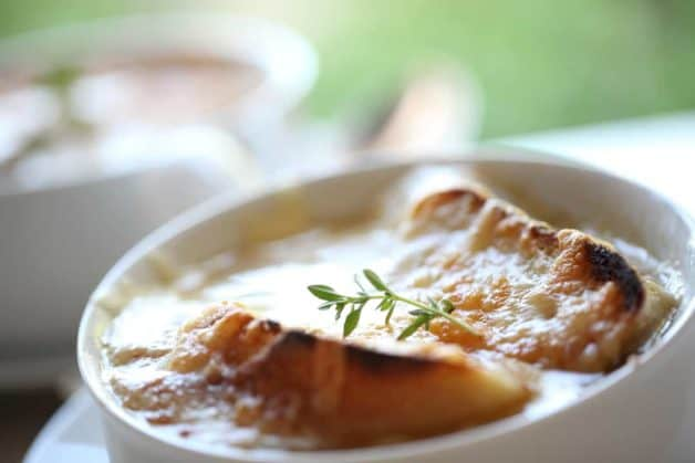 French Onion Soup Recipe in a shallow bowl with sprig of thyme on top