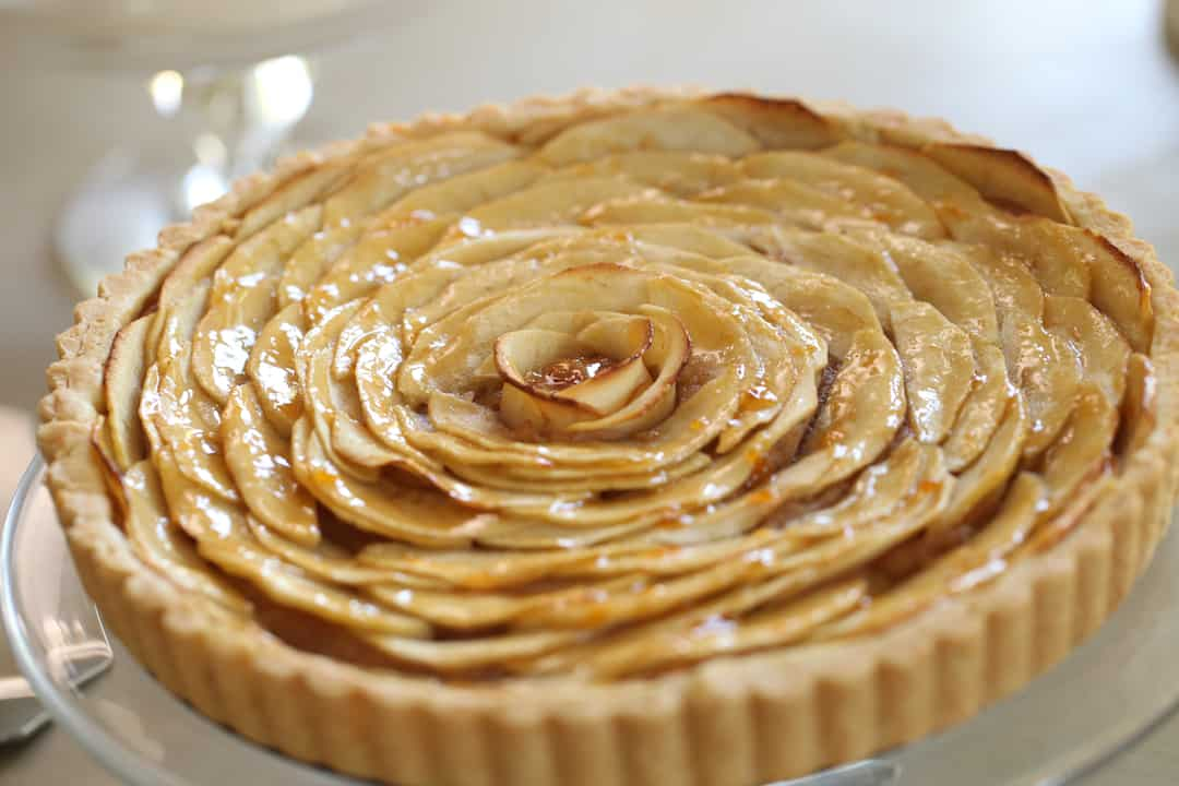 Classic French Apple Tart Recipe on a cake stand