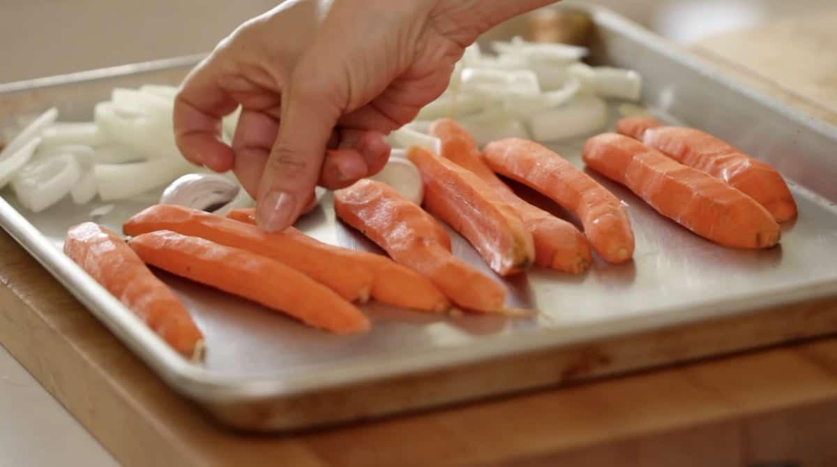 adding whole carrots to a sheet pan