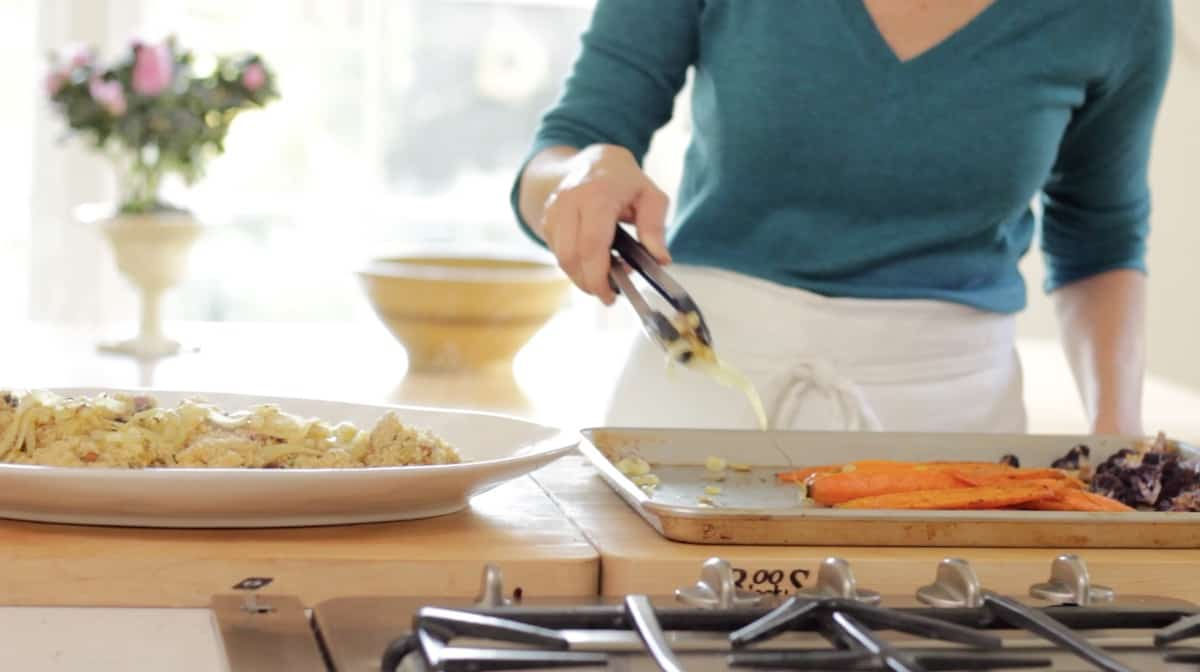 Placing vegetables on a platter from a sheet pan
