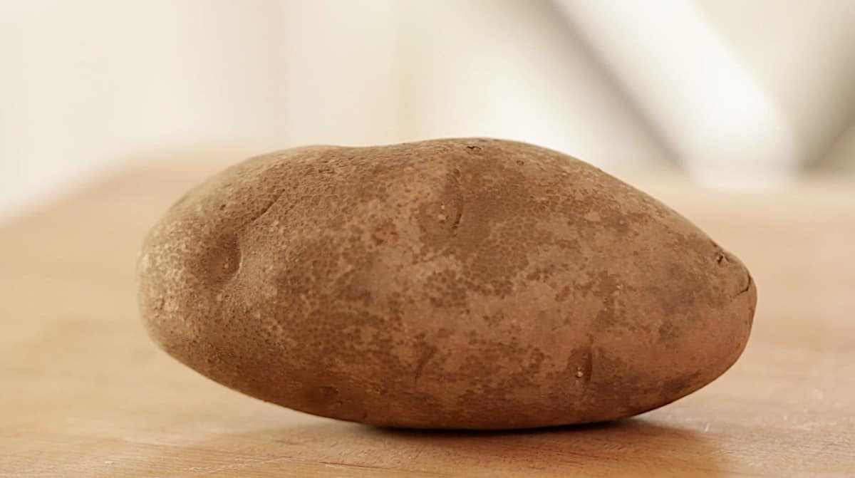 a russet potato on a board
